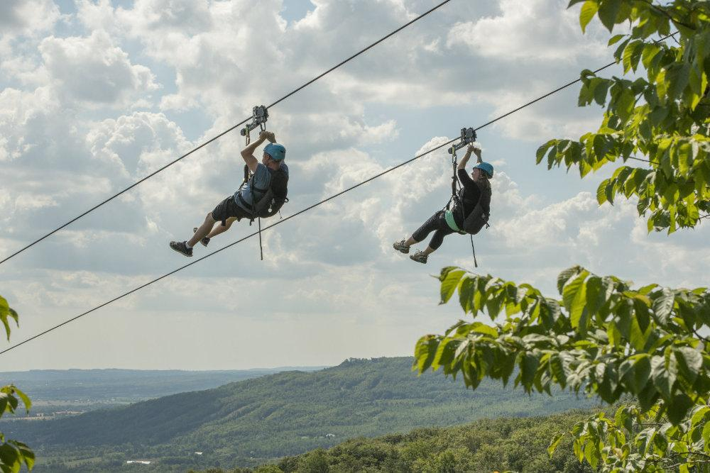 Two people zip lining over the trees at Blue Mountains Scenic Caves